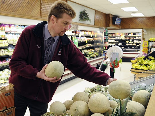 Merlin Jeffery, owner of Quality Foods Hometown Markets stocks cantaloupe in the West Grand Avenue store in Wisconsin Rapids.