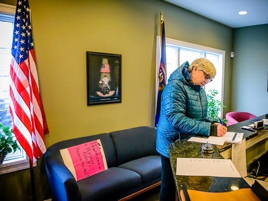Catherine Allen of East Lansing , a Move On and Indivisible of Lansing member, signs in at U.S. Representative Mike Bishop's office before presenting a letter to Stuart Pigler ,Deputy District Director of Bishops' office during a protest by members of Indivisible Group of Lansing Monday January 30, 2017 in Brighton.  KEVIN W. FOWLER PHOTO