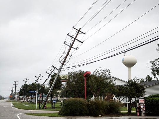 A row of utility polls lean from the strong winds of