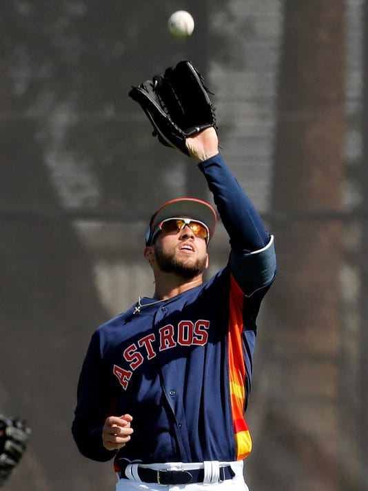 Houston Astros outfielder George Springer catches a pop fly during spring training baseball practice Monday, Feb. 19, 2018, in West Palm Beach, Fla. (AP Photo/Jeff Roberson)