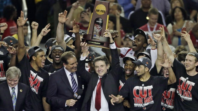 Louisville coach Rick Pitino celebrates with his team after beating Michigan to win the 2013 men's basketball national title.