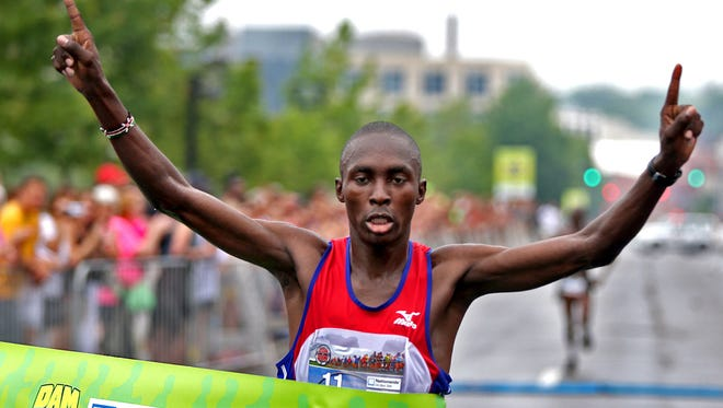 Sammy Rotich, of West Des Moines, at the finish line to take first place in the Dam To Dam half marathon men's race in downtown Des Moines on Saturday morning May 31, 2014.