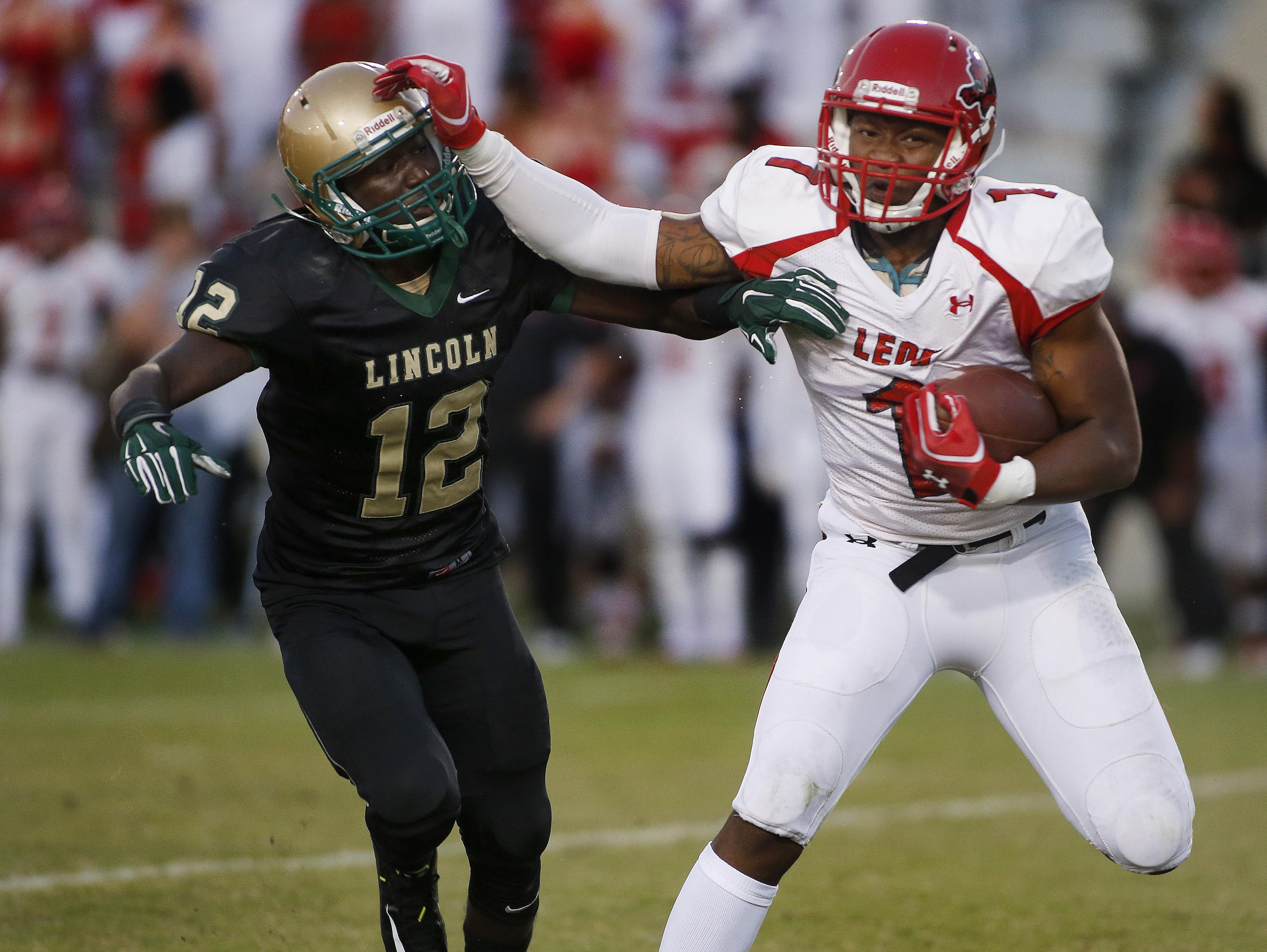 Leon alum D'anfernee McGriff delivers a stiff arm to Lincoln's Giovanni Weekley during a 2014 run. McGriff rushed for over 2,000 yards as a junior quarterback.