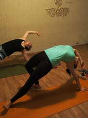 Students stretch and bend at a yoga class at Twisted