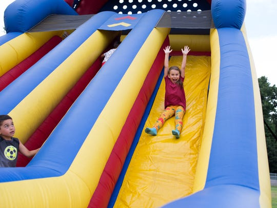 Grace Rodriguez rides down an inflatable slide at the