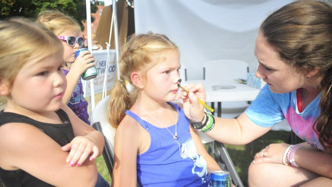 Faith Wharton, 8, of Bellville, gets her face painted by Hallie Gottfried, as her sisters look on.