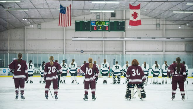 The teams listen to the national anthem during the girls hockey game between Northfield vs. Burlington/Colchester at Leddy Ice Rink on Saturday afternoon