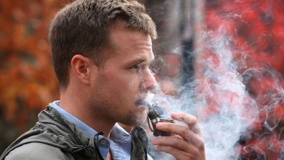 University of Kentucky law student Seth Thomas, who said he was not a regular smoker, smokes a pipe in the free speech area outside the Student Center on the university's campus in Lexington, Ky. on Thursday, Nov. 19, 2009 in protest of the school's smoking ban. Kentucky's flagship public university gave the official heave-ho to tobacco on Thursday, touting the health benefits of a smoke-free policy covering all of its sprawling campus in the heart of burley tobacco country. (AP Photo/The Lexington Herald-Leader, David Perry) ORG XMIT: KYLEL101