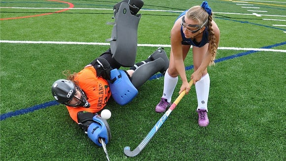 Kelsey McCrudden lifts ball after rebound over goalie Kellie Smith during Tuesday's Lakeland field hockey practice..