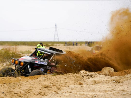A racer digs deep into soft dirt on a turn near the