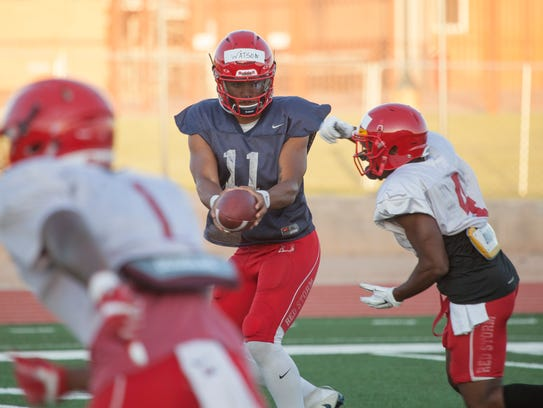 Dixie State quarterback Malik Watson hands the ball