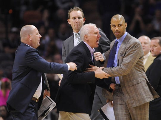 "In this Jan. 17, 2014, file photo, San Antonio Spurs coach Gregg Popovich, middle, is held back by assistant coaches Jim Boylen, left, Sean Marks, top, and Ime Udoka as he argues with officials during second-half NBA action against Portland in San Antonio, Texas. The Brooklyn Nets have hired Sean Marks of the San Antonio Spurs as their general manager. Nets owner Mikhail Prokhorov on Thursday, Feb. 18, 2016, lauded Marks for his coaching and management experience, saying it ""gives him a 360-degree view of the job at hand.""(Bill Calzada/San Antonio Express-News via AP)"