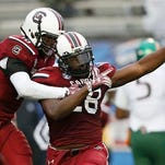 South Carolina linebacker Jonathan Walton (28) celebrates his interception of a Miami pass with Skai Moore, left, in the first half of the 2014 Independence Bowl.