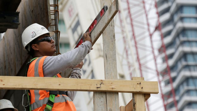 In this Friday, May 16, 2014 photo, a construction worker works on the site of the SoMa at Brickell apartment building in downtown Miami. The Labor Department reports revised figures for productivity in the first quarter on Wednesday, June 4, 2014. (AP Photo/Lynne Sladky) ORG XMIT: NYBZ117