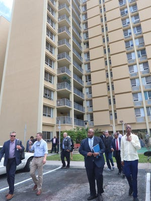 Nathan Simms, second from right, leads developers, lenders and others interested in affordable housing on a tour of the Daytona Beach Housing Authority's properties, including the Maley complex in the background, in  April last year. Simms is the Housing Authority's director of development and was attempting to attract private dollars and projects to renovate or replace many of the city's aging units.