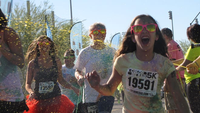 Color Run participants are sprayed with color as they race at Goodyear Ballpark.