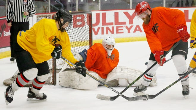 The orange team attempts to defend the goal against the gold team Saturday at the JDRF Hockey Tournament at First Arena.
