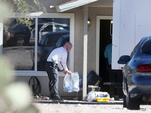 Tucson Police Department investigators and evidence technicians investigate the scene at a home where two people were arrested Tuesday after three girls told authorities that they have been imprisoned