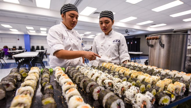 Culinary student Zandra Rupido, left, makes a final check of a sushi tray, minutes before the opening of a Japanese buffet at the Guam Community College in Mangilao on Thursday, April 5, 2018. Students taking the Pacific and Asian Cuisine course prepared a variety of dishes to include sushi, vegetable tempura, soups, yakisoba, teriyaki chicken and desserts for the all-you-can-eat meal, which costs diners $10. On Thursdays during the month of April, the buffets will continue with a different Asian-themed menu featured, said chef Paul Kerner, course instructor.