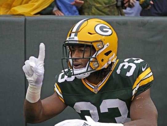 """Green Bay Packers running back Aaron Jones (33) celebrates his first quarter touchdown by flashing """"9-1-5"""" during the Green Bay Packers vs. New Orleans Saints NFL football game at Lambeau Field in Green Bay, Wisconsin, Sunday, October 22, 2017. Milwaukee Journal Sentinel photo by Rick Wood/RWOOD@JOURNALSENTINEL.COM"""