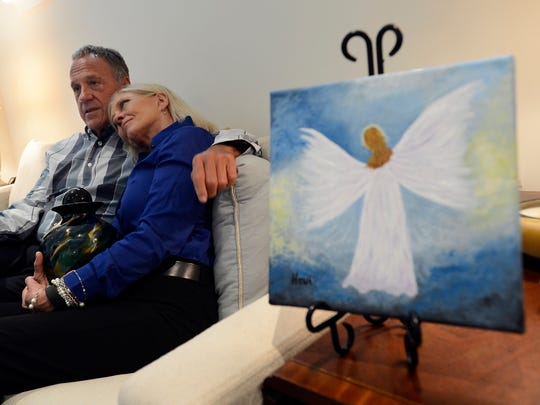 Bruce and Betty Mason at their home with a painting their cousin Hewi Mason painted on the day Bruce and Betty's daughter died.