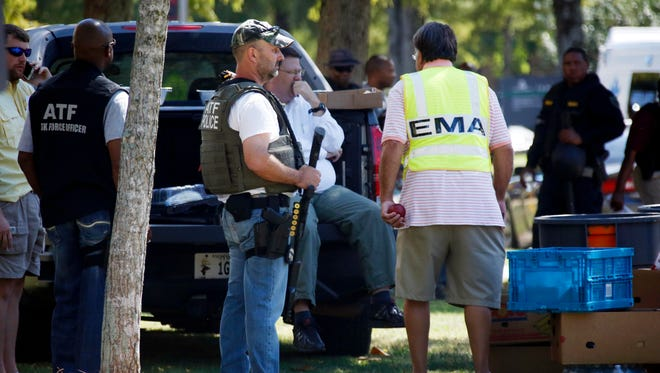 Law enforcement officers gather on the Delta State University campus to search for an active shooter in connection with a the shooting of history professor Ethan Schmidt in his office Monday in Cleveland. The suspect in the shooting remains at large.