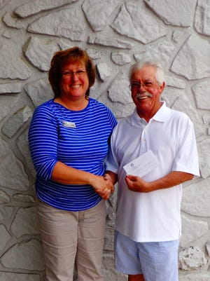 Regan Curnutt, Mountain Home Elks Lodge 1714 secretary, presents $300 to Julie Fienhold, Mountain Home Challenged Athletes Booster Club president. The donation was for a Special Olympics Golf Tournament fundraiser at Twin Lakes Golf Course.
