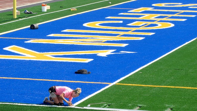 Missy Kisner from Field Turf works on the north end zone at Bremerton Marmoreal Stadium on Tuesday. The stadium is changing from natural grass to turf.