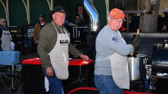 Brian Walser and John Dickinson pose for a photo while cooking Sunday morning for the annual Iron Horse Pub customer appreciation Super Bowl party.