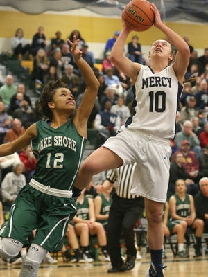 Mercy's Leah Koonmen draws the foul on Lakeshore's Tashawni Cornfield as she drives to the basket during their Class A Far-West Regional game on March 5, 2016 at Rush-Henrietta High School.