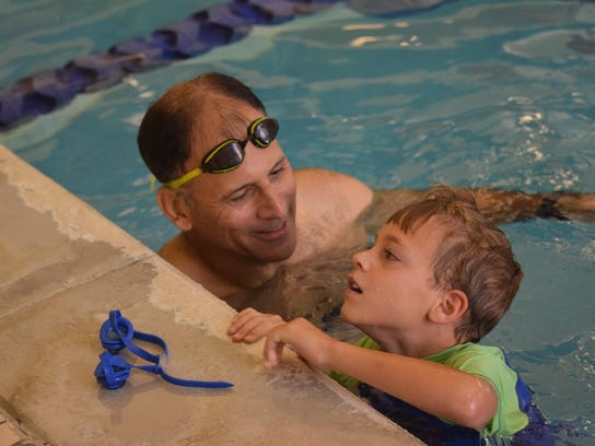 """ANI Swim Clinic Louis Guidry (left), a triathlete, talks with Luca Olagues, 7, during a """"Swim + Transition Tips Clinic"""" held Saturday, Aug.15, 2015 at the Louisiana Athletic Club in Pineville. Children registered for the Wild Kidz Tri practiced swimming in"""