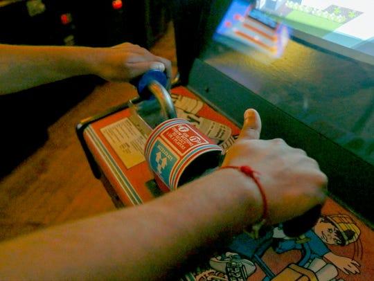 Hershel Vasani, of Detroit, grabs onto the video game