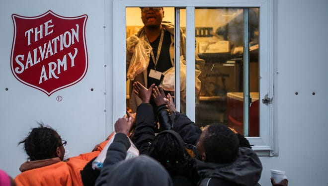 "Children who live at the Sojourner Truth Housing Project reach toward the Bed and Bread program food truck as Lannell Smith, 43, of Detroit, hands out Lunchables on March 2, 2017. ""You ought to see the look on their faces when they get those bags,"" said driver Gregory Taylor of the kids. ""It's like Christmas. That makes my day, the looks on those faces."""