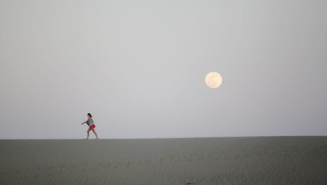 A visitor walks along on the Mesquite Flat Sand Dunes at Death Valley National Park on Tuesday, March 22, 2016 in Death Valley, Calif.