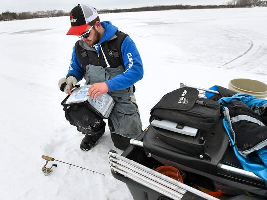 Grant Hopke, St. Augusta, searches his arsenal for just the right bait while fishing Wednesday, Jan 27 on Beaver Lake near Luxemburg.