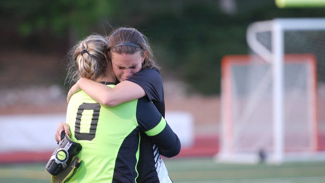 Rocky Mountain's Gabriella McDonald, left, and Savannah Warner hug after Wednesday's quarterfinal loss to Grandview.