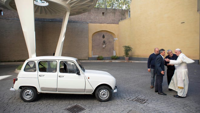In this Sept. 7, 2013, picture made available by the Vatican newspaper l'Osservatore Romano, Pope Francis, right, speaks with the Rev. Renzo Zocca, second from right, and owner of the Renault 4L seen at left, his assistant Luigi Macchioni, and car-body repairer Stefano Veronesi, fourth from right, after the car was donated by Zocca, at the Vatican.