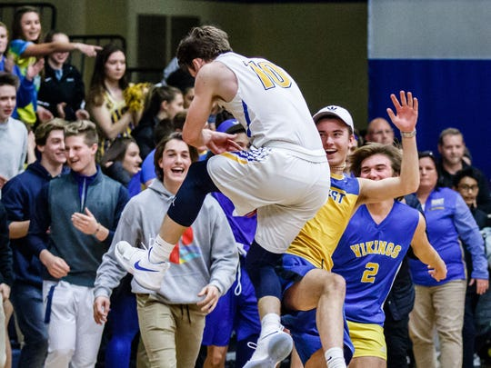 New Berlin West senior Joe Robey (10) celebrates with the student section after scoring the winning basket in overtime against visiting New Berlin Eisenhower on Tuesday, Jan. 23, 2018.