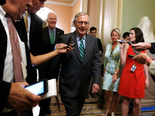 Senate Majority Leader Mitch McConnell of Ky., center, followed by Majority Whip John Cornyn, R-Texas, leaves a Republican meeting on healthcare, Thursday, June 22, 2017, on Capitol Hill in Washington. Senate Republicans would cut Medicaid, end penalties for people not buying insurance and erase a raft of tax increases as part of their long-awaited plan to scuttle Barack Obama's health care law. (AP Photo/Jacquelyn Martin)