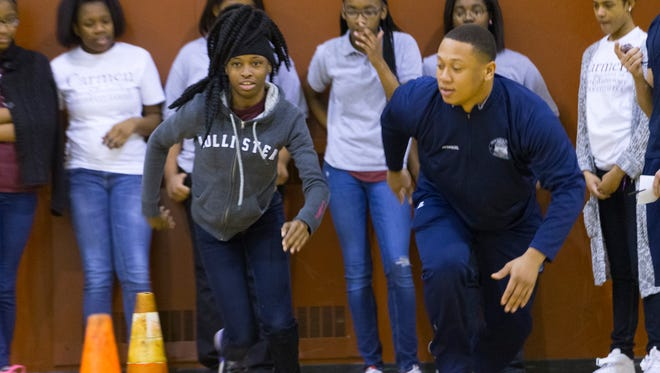 Seventh-grader Precious Dean (left) is coached in an agility drill with Milwaukee police recruit Martinese McDaniel on Friday.