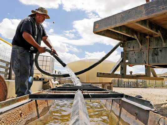 Richard Root, an equipment operator for the Shiprock Chapter house, fills up a trough for livestock at a home in Shiprock on Aug. 11. Last month, an abandoned mine north of Silverton, Colo., spewed toxic wastewater into the Animas and San Juan rivers, forcing officials to close access to the rivers.