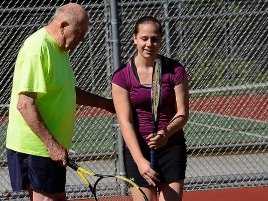 Vince Kingston helps Tori Austin, 15, with her form during the Tennis for Kids program on Wednesday at the Red Lion High School tennis complex.