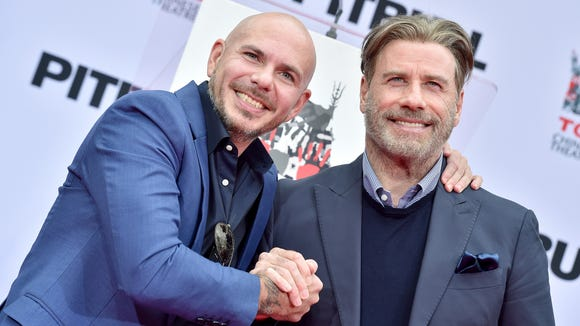 Pitbull is all smiles with John Travolta. But he had hair concerns.