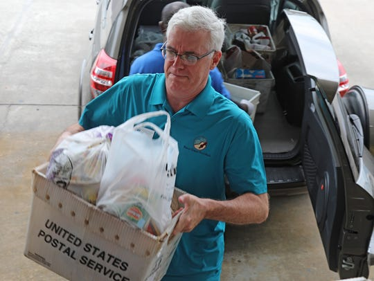 Harry Chapin Food Bank CEO Richard LeBer helps unload