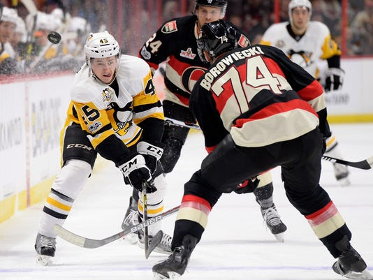 Pittsburgh Penguins' Josh Archibald (45) chips the puck past Ottawa Senators' Mark Borowiecki (74) during the first period of an NHL hockey game in Ottawa, Ontario, Thursday, March 23, 2017. (Justin Tang/The Canadian Press via AP)