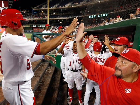 Washington Nationals' Ben Revere, left, celebrates after scoring during the eighth inning of a baseball game at Nationals Park, Tuesday, Sept. 6, 2016, in Washington. The Nationals won 9-7. (AP Photo/Alex Brandon)