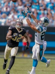 Carolina Panthers' Christian McCaffrey (22) stretches to make the catch as New Orleans Saints' Kenny Vaccaro (32) can only watch during the second half of an NFL football game in Charlotte, N.C., Sunday, Sept. 24, 2017. The Saints won 34-13.