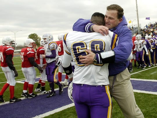 Munday head coach Patrick Corcoran hugs senior lineman Samuel Nunez following the Moguls' 26-6 victory  over Bremond in Saturday afternoon's Class A Division II championship game in Stephenville.