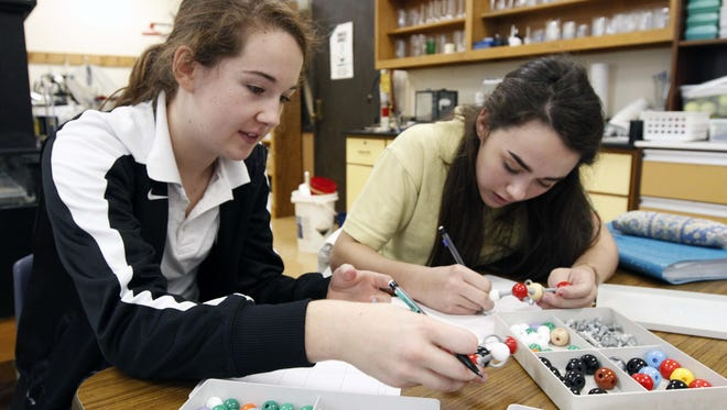 Female students work out chemistry problems with plastic models.
