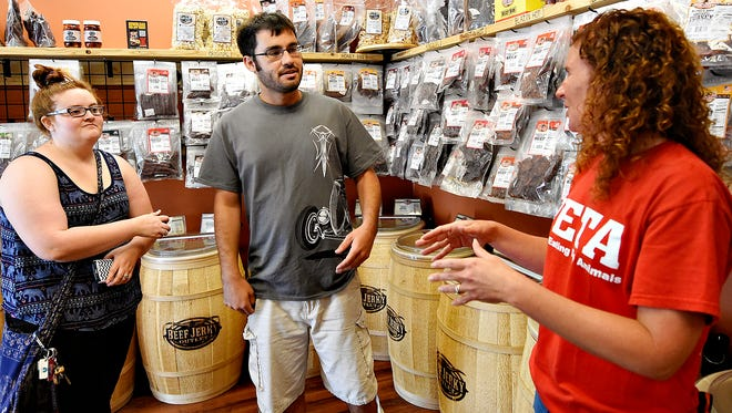 Assistant Manager Melissa Wolfe, of Beef Jerky Outlet, right, discusses levels of heat with Tori Houk, left, of Penn Township, and Will Hernandez, of Springettsbury Township, during their first visit to the store in York, Monday, June 6, 2016.  In celebration of National Beef Jerky Day, the store will be offering sales and giveaways as well as donating 5 percent of the purchase price, for sales made June 10-12, to the Wounded Warrior Project. Dawn J. Sagert photo